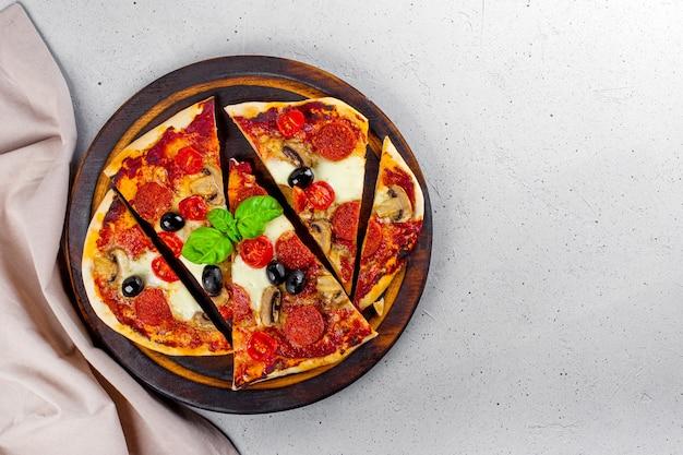 Świeża domowa włoska pizza z mozzarellą, kiełbaskami pepperoni, oliwkami i bazylią na desce do krojenia widok z góry