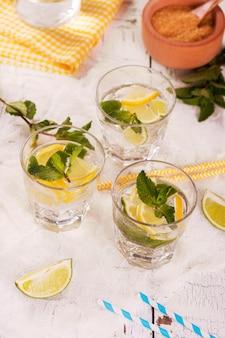 Świeża domowej roboty lemoniada cytrynowa i limonkowa podawana z miętą, kostkami lodu i słomkami