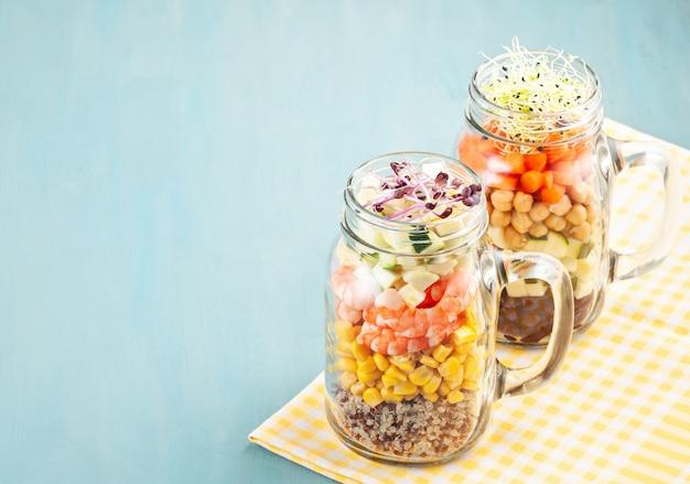 Świeża domowej roboty sałatka w słoikach z komosą ryżową, ciecierzycą i organicznymi warzywami. zdrowe jedzenie, wegetariańskie, detox koncepcja