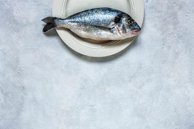 Świeża dorado ryba na białym naczyniu na bielu stole