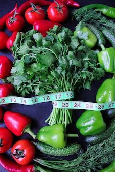 Świeża ekologiczna pietruszka, pomidory, czerwona papryka, zielona papryka, koper włoski, koperek i ogórek z zielonym centymetrowym widokiem z góry, pojęcie diety