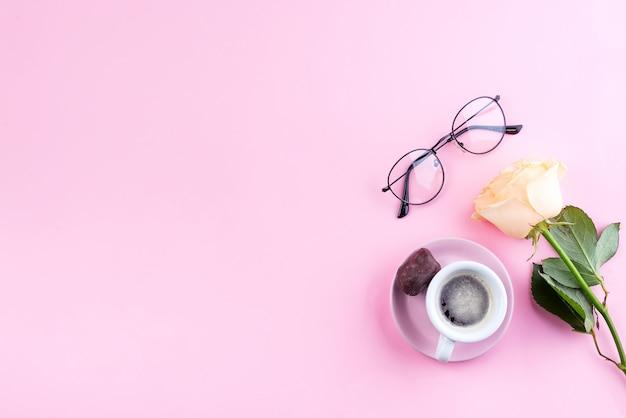 Świeża filiżanka kawy, szklanki i beżowe pachnące róże na pastelowym różowym tle, płaskie świecenie