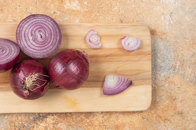 Świeża fioletowa cebula umieszczona na drewnianej desce do krojenia.