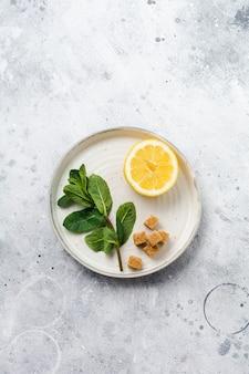 Świeża gałąź mięty, cytryny i kawałki cukru trzcinowego na płycie ceramicznej na starym tle betonu.