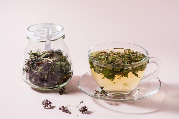 Świeża gorąca herbata z oregano w filiżance i suszone ziele w słoiku. ziołolecznictwo i terapia alternatywna