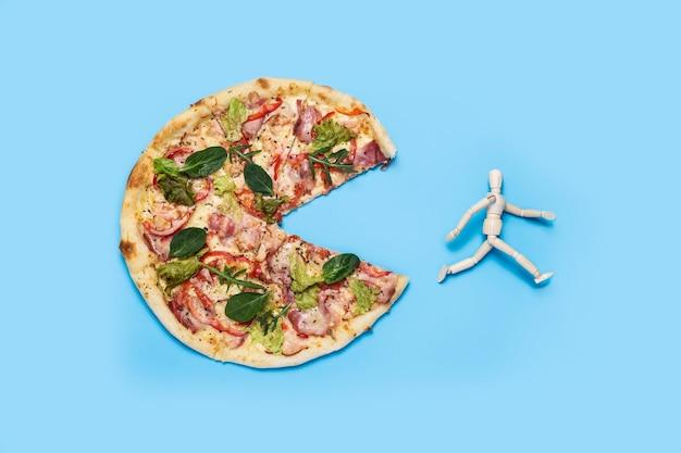 Świeża gorąca pizza i działa marionetka na niebiesko. pojęcie diety, prawidłowe odżywianie