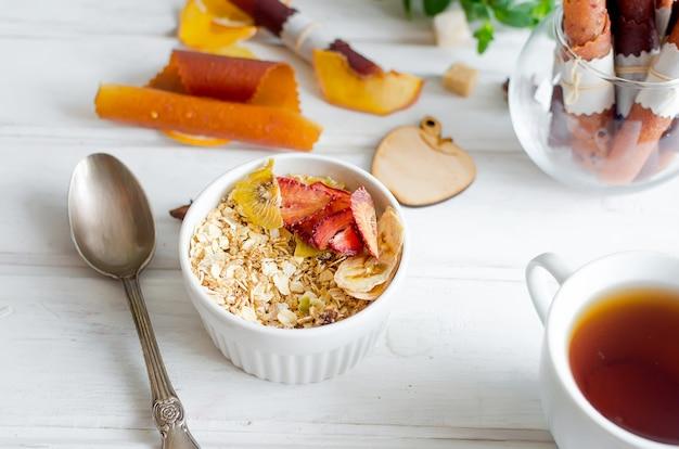 Świeża granola, musli z migdałami, orzeszkami ziemnymi, nasionami i różnymi owocami, chipsami i cukierkami pastylki w białym talerzu na białym drewnianym tle, selektywne focus, detox koncepcja zdrowej żywności, miejsce