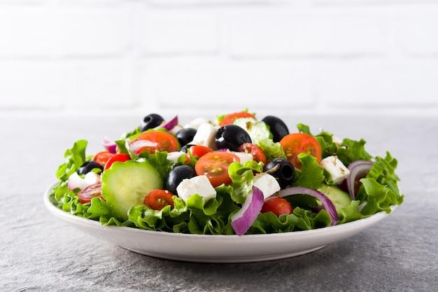 Świeża grecka sałatka w talerzu z czarną oliwką, pomidorem, serem feta, ogórkiem i cebulą na szarym tle