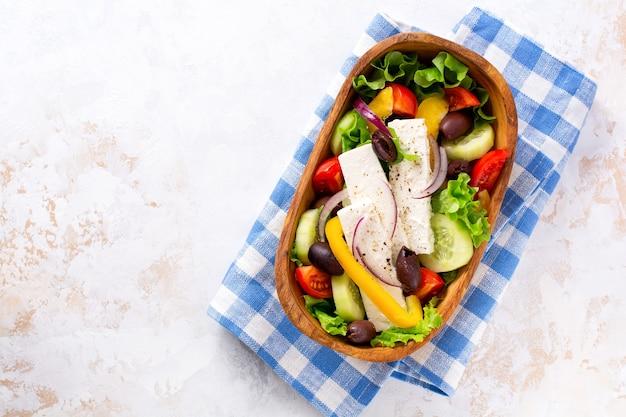 Świeża grecka sałatka z pomidorem, ogórkiem, papryką, oliwkami i serem feta na drewnianym talerzu. tradycyjne greckie danie. zdrowa żywność, widok z góry