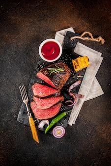 Świeża grillowana wołowina, domowe mięso z grilla średnio rzadkie, na desce do krojenia z czarnego kamienia, z przyprawami