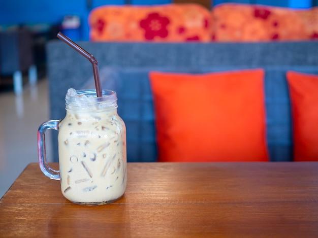 Świeża herbata mleczna w szklance umieszczonej na drewnianej podłodze. z wolną przestrzenią