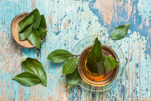 Świeża herbata od liścia laurowego w filiżance na drewnianym wieśniaka stole
