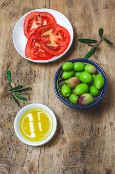Świeża hiszpańska oliwa z oliwek z pierwszego tłoczenia z oliwkami i pomidorami