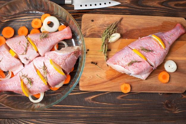 Świeża i gotowa do przyrządzenia surowa różowa ryba okoń z dodatkami takimi jak cytryna