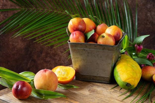 Świeża i pyszna brzoskwinia i mango w metalowym koszu. składniki na koktajl owocowy z owoców tropikalnych