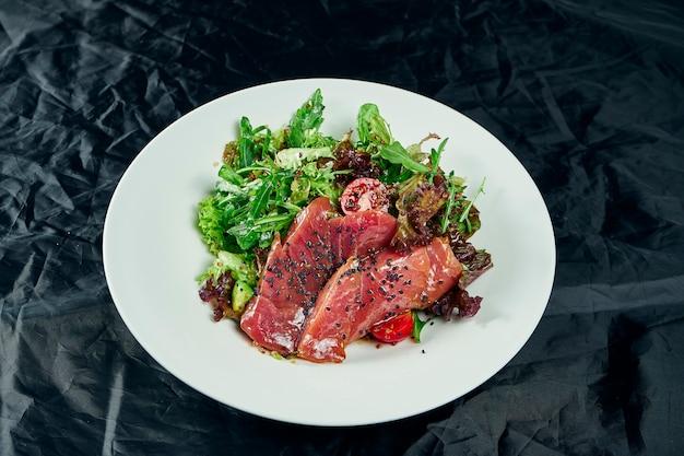 Świeża i pyszna sałatka tataki z tuńczykiem, sałatą, awokado. smaczna sałatka z owoców morza kuchni japońskiej w białej misce na drewnianym stole. zdjęcie żywności z bliska