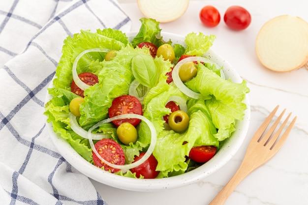 Świeża i zdrowa sałatka z sałatą, cebulą, pomidorem cherry i oliwkami w misce. jedzenie środziemnomorskie