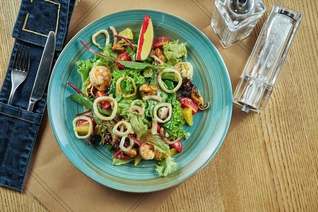 Świeża i zielona sałatka z owocami morza (krewetki, kalmary, małże, przegrzebki), pomidorami koktajlowymi w niebieskim talerzu na drewnianym stole. ustawienie stołu w restauracji