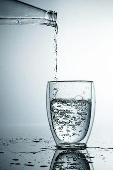 Świeżą i zimną, czystą wodę wlewa się do szklanki. oczyszczona woda w szklance na szarej ścianie. motion freeze splash kryształowej wody na szarej ścianie.