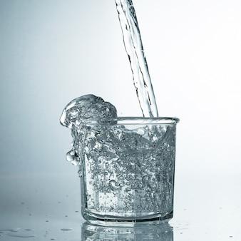 Świeżą i zimną, czystą wodę wlewa się do szklanki. oczyszczona woda w szklance na szarym stole. motion freeze splash kryształowej wody na szarym stole.