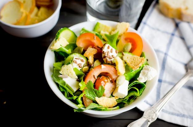 Świeża jasnozielona sałatka z ogórkiem, sałatą, awokado, pomidorami do lanchu na ciemnym drewnianym stole. pojęcie zdrowej żywności. leżał na płasko.