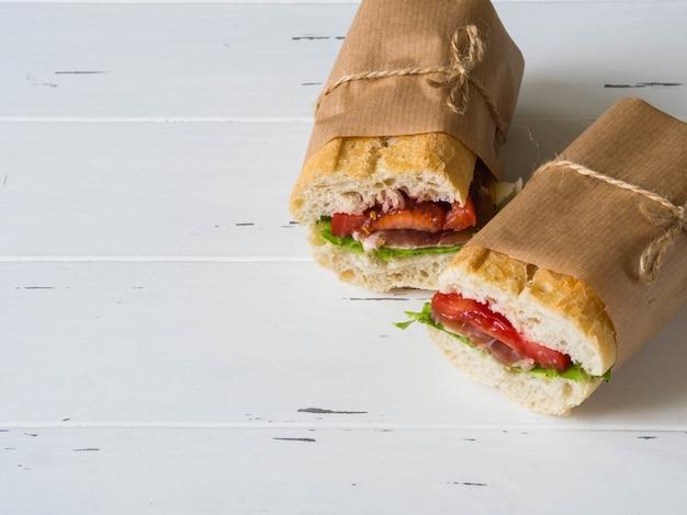 Świeża kanapka z bagietką z mięsem, serem w plasterkach, pomidorami i świeżą sałatą