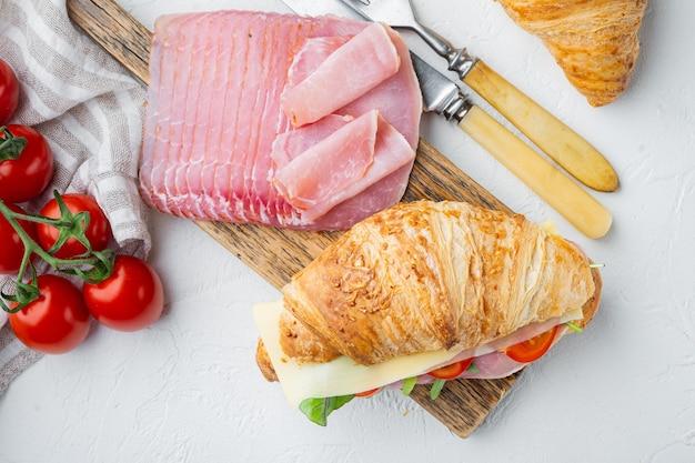 Świeża kanapka z rogalikiem z szynką, serem i zestawem liści sałaty, z ziołami i składnikami, na białym kamiennym tle, płaski widok z góry