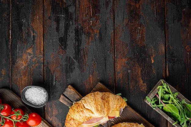 Świeża kanapka z rogalikiem z szynką, serem i zestawem liści sałaty, z ziołami i składnikami, na starym ciemnym drewnianym stole, widok z góry na płasko, z miejscem na tekst