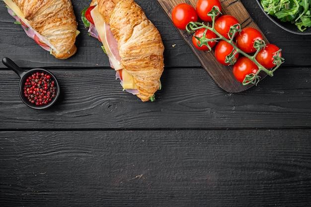 Świeża kanapka z rogalikiem z szynką, serem i zestawem liści sałaty, z ziołami i składnikami, na tle czarnego drewnianego stołu, płaski widok z góry, z miejscem na tekst
