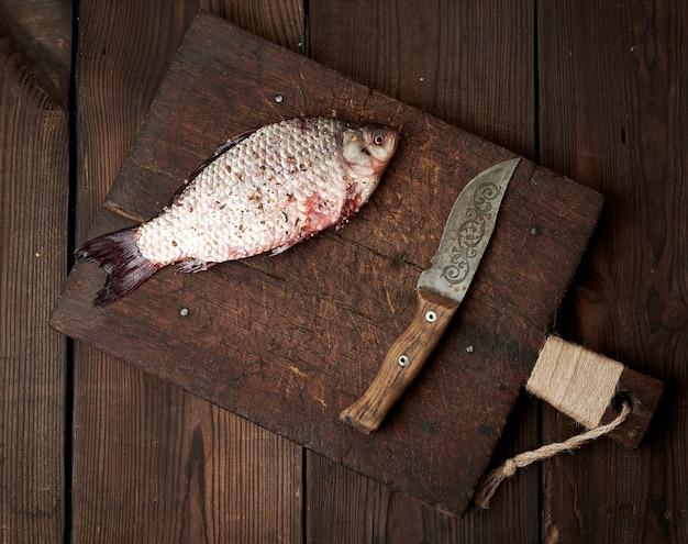 Świeża karaś posypana przyprawami leży na brązowej drewnianej desce do krojenia