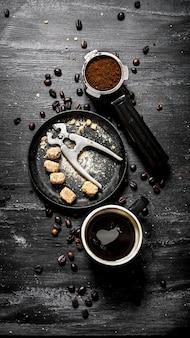Świeża kawa. filiżanka kawy z brązowym cukrem i prażonymi ziarnami. na czarnym tle rustykalnym.