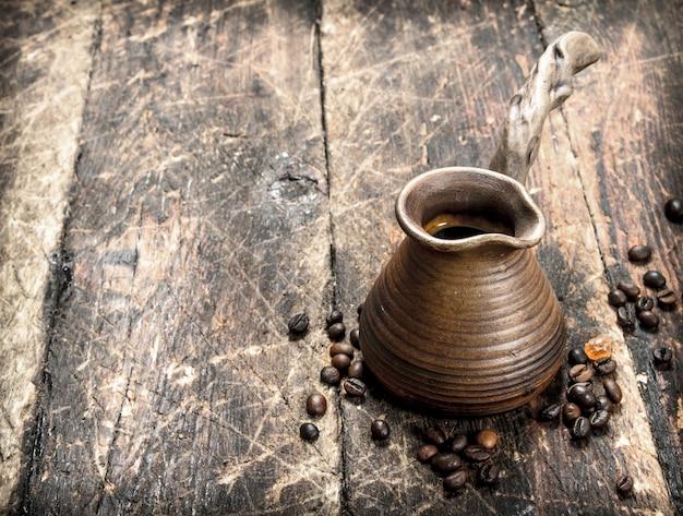 Świeża kawa w glinianym indyku. na drewnianym tle.