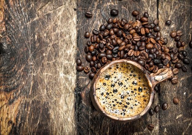 Świeża kawa w glinianym kubku. na drewnianym tle.
