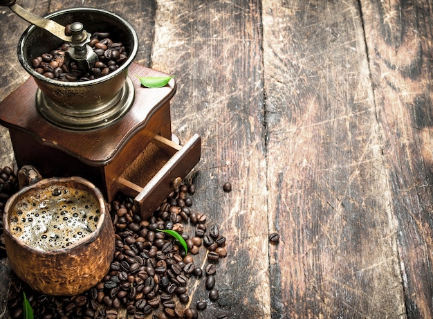 Świeża kawa w glinianym kubku ze starym młynkiem do kawy. na drewnianym tle.