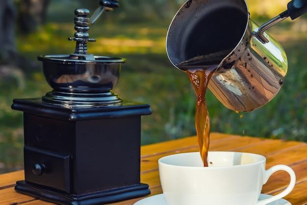 Świeża kawa z cezve wlewająca się do filiżanki