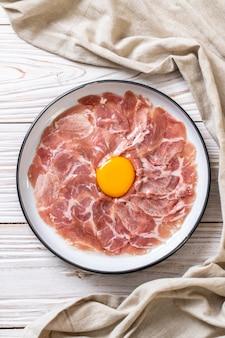 Świeża krojona wieprzowina surowa z jajkiem