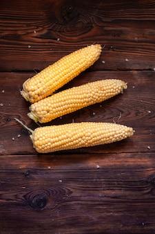 Świeża kukurydza na ciemnym drewnianym stole. widok z góry.