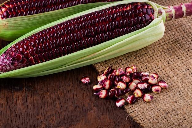 Świeża kukurydza na kolbach na rustykalnym drewnianym stole, zbliżenie