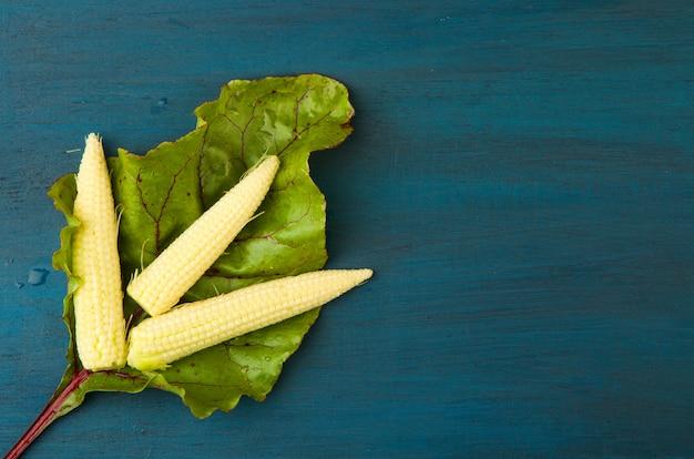 Świeża kukurydzy świeżego liścia pod jasną drewniową powierzchnią.