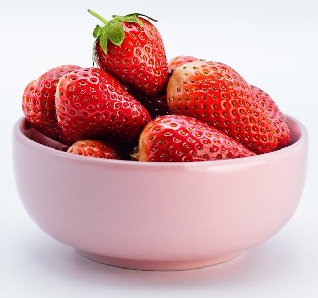 Świeża lato truskawka z liściem w różowym pucharze odizolowywającym na bielu