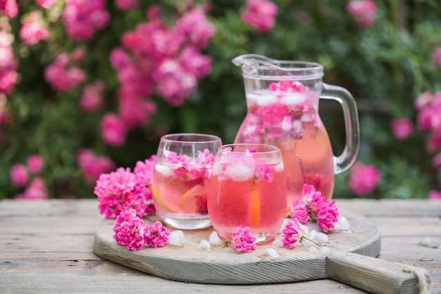 Świeża lemoniada różana z lodem i świeżymi różami w naturalnym ogrodzie