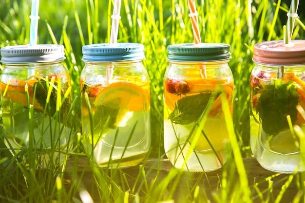 Świeża lemoniada w słoikach ze słomkami. hipsterskie letnie drinki. ekologiczny w naturze. cytryny, pomarańcze i jagody z miętą w szklance. zielona wysoka trawa na zewnątrz.