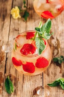 Świeża lemoniada z zieloną herbatą limonkową miętą i truskawką na drewnianym tle zimne lato pić dwie szklanki z selektywną ostrością jagodowej herbaty lodowej