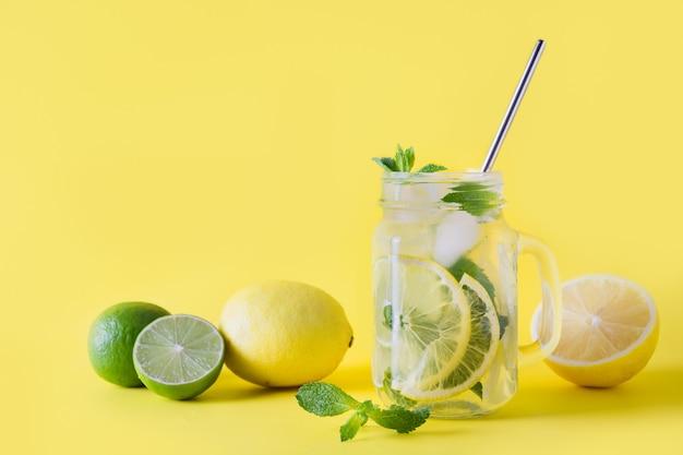 Świeża letnia lemoniada z cytryną, limonką, pomarańczą i miętą na żółtym tle.