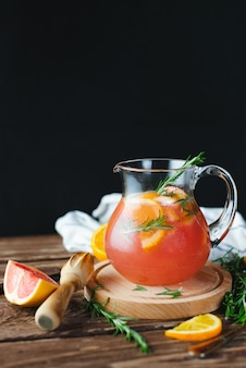 Świeża letnia lemoniada z grejpfrutem i rozmarynem na starym drewnianym stole. koncepcja lato.