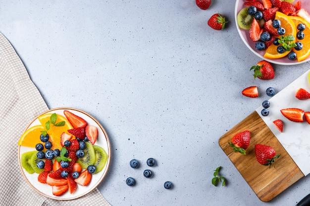 Świeża letnia sałatka z różnych owoców i jagód. kiwi, pomarańcza, truskawka i jagoda na talerzu ozdobionym miętą na blacie stołu.
