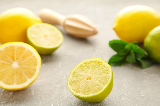 Świeża limonka, cytryna i mięta z sokowirówką cytrusową na szarej ścianie. składnik preparatu do gotowania z limonką i cytryną.