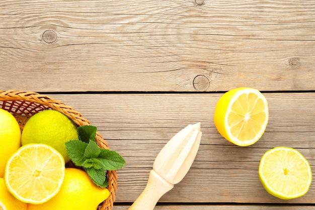Świeża limonka i cytryna w koszu z sokowirówką cytrusową na szaro. składnik preparatu do gotowania z limonką i cytryną.