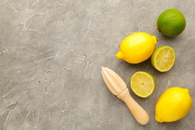 Świeża limonka i cytryna z sokowirówką cytrusową na szaro. składnik preparatu do gotowania z limonką i cytryną.