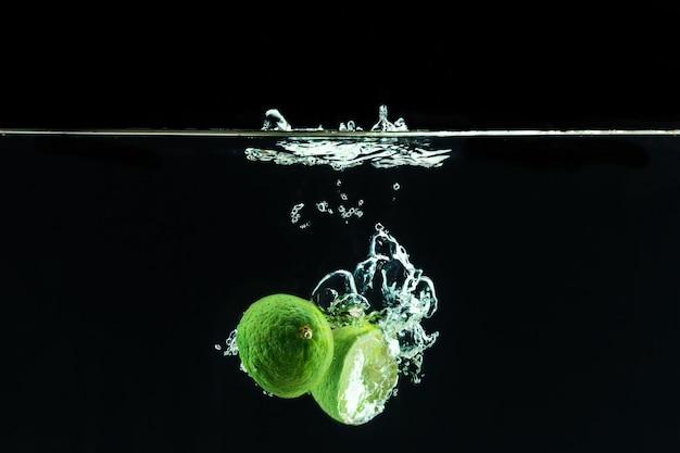 Świeża limonka wrzucona do wody z pluskiem
